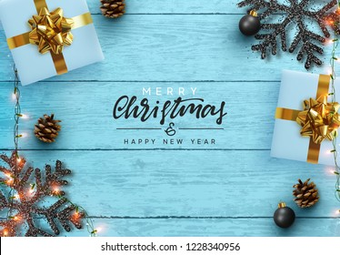 Christmas composition on wooden background. Xmas decoration design, box gift, snowflake color black, gold garland, pine cone. Blue realistic Wood texture. Flat lay, top view.