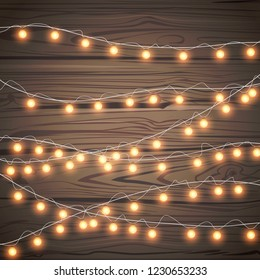 Christmas garlands isolated on wooden background. Xmas realistic overlay golden lights card. Holidays decorations bright garland lamps set. Vector gloving bulb illustration decor