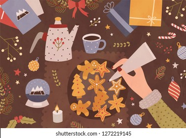 Christmas greeting card template with hand holding pastry bag and decorating cookies, cup of tea, teapot and festive seasonal decorations lying on table. Colorful vector illustration in flat style.