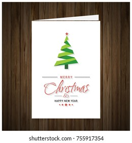 Christmas Greeting Card. Wooden background with painted holiday typography and Christmas tree.