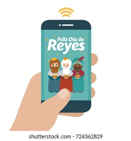 Christmas is here. Send your letter to The three wise men of orient from your cell phone. Hand holding smartphone. Happy day of kings written in spanish