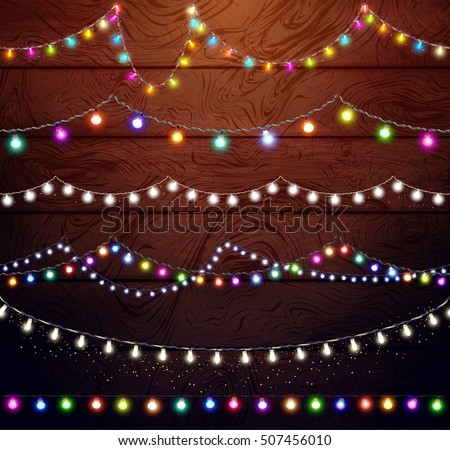 Christmas lights set, colored garlands, New Year design,festive decorations  on wooden background - Christmas Lights Set Colored Garlands New Stock Vector (Royalty Free