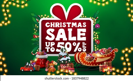 Christmas sale, up to 50% off, green discount banner with large cartoon present with large offer decorated with Christmas tree branches, candy, garlands and Christmas presents