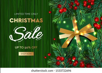 Christmas Sale banner. Realistic fir-tree branches with berries and green gift box on wooden green background. Vector illustration for winter holiday discounts