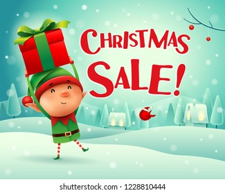 Christmas Sale! Little elf holds up gift present in Christmas snow scene winter landscape.