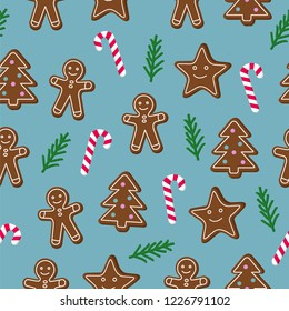 Christmas seamless pattern. Brown gingerbread man and Christmas Tree and star cookies with lolipop candy cane and green spruce tree twig on blue background. Graphic design element for wrapping paper