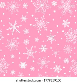 Christmas seamless pattern with various complex big and small snowflakes, white on pink background