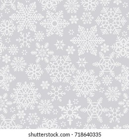 Christmas seamless pattern with white snowflakes on gray background. Winter New Year pattern.