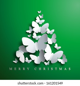 Christmas tree made of white paper butterflies on green background