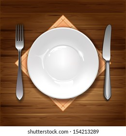 Clean plate with knife, fork and napkin on wooden background.