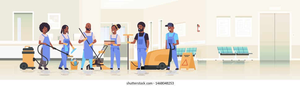 cleaners team in uniform working together cleaning service concept african american janitors using professional equipment clinic reception hospital corridor interior flat full length horizontal