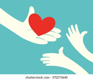 Close up of hand holding red heart and hands of children on green background