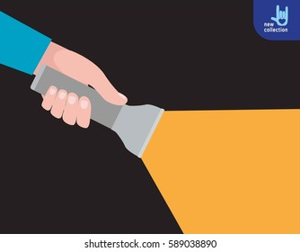 Close up. Hand holding torch light shining forward in the dark