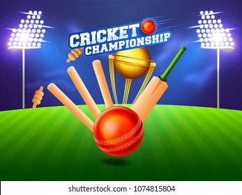 Close view of a cricket wickets, bat, ball and winning trophy on night stadium background.