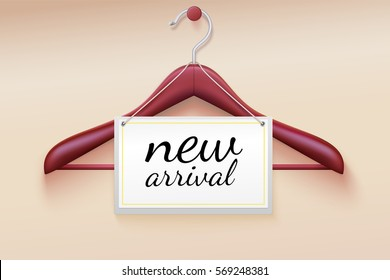 Clothes hanger with new arrival tag. Wooden hanger with tag and the message about the new delivery of the goods