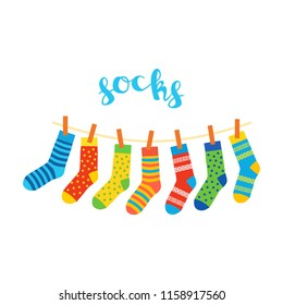 colored socks hanging on a rope on white background