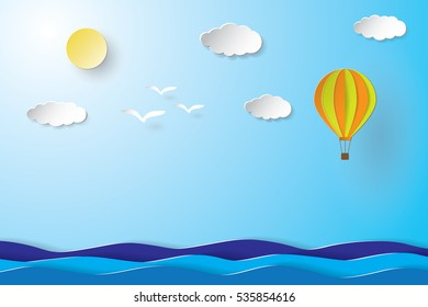 Colorful hot air balloon and cloud over the sea. paper art style.