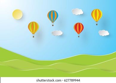 Colorful hot air balloon and sun over green field. paper art style.