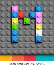 Colorful letter M from building lego bricks on gray lego background. Lego letter M