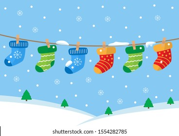 Colorful pairs of socks hanging on the rope. Winter landscape.