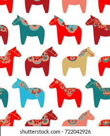Colorful seamless vector pattern with Scandinavian Christmas dala horses on white background