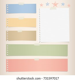 Colorful striped note, notebook paper for message or text stuck with sticky tape on brown background.