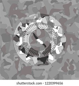 combat knife icon inside grey camouflaged emblem