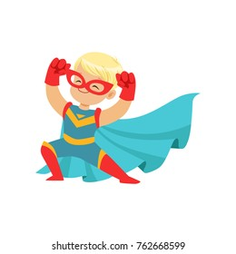 Comic happy kid in superhero costume, red mask and gloves, blue cape developing in the wind, posing and showing muscles.