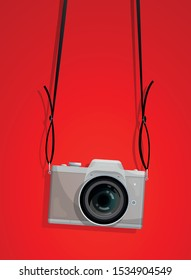 Compact photocamera with belt on the red background