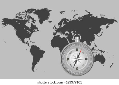 the compass on the grey map of the world indicating the direction