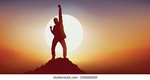 Concept of leadership with a man who expresses his joy by raising the point in a sign of victory by reaching the summit of a mountain