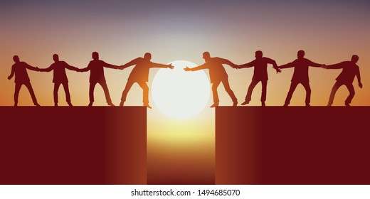 Concept of teamwork with two groups of men, separated by a chasm that tries to meet by holding each other to successfully overcome the obstacle.
