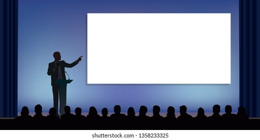 At a conference, a businessman standing behind a desk, points to a white screen to present a project in front of an audience.