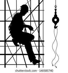 Construction worker is climbing on metal scaffolding. Silhouette.
