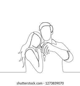 continuous line drawing of couple holding a key looks happy after purchase house or home - Vector illustration isolated on white background