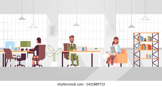 corporate staff employees working in creative co-working open space coworkers businesspeople sitting at workplace and discussing new project modern office interior flat full length horizontal