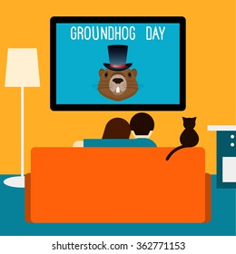 Couple and cat watching television sitting on couch in  room. Groundhog day theme.  Groundhog day card. Couple on couch and tv. Room interior. Cat on couch. Couple at home. Interior with couch and tv.