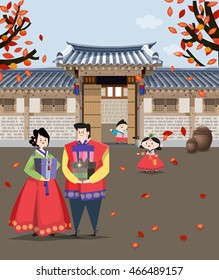 A couple dressed in Korean traditional costume having gifts for the national holiday and  Korean style house behind.