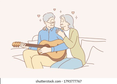 Couple, love, play, romance, music, recreation concept. Romantic old man and woman senior citizens pensioners sitting on couch together and playing guitar musical instrument at home. Happy retirement.