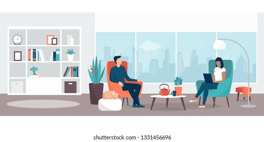 Couple relaxing at home sitting on the armchairs  in the living room, the woman is connecting with her laptop, lifestyle and interior design concept