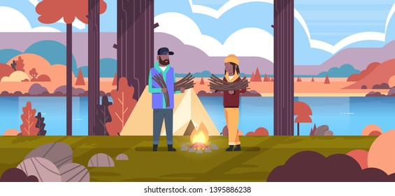 couple tourists hikers holding firewood african american man woman organizing fire n camp tent hiking camping concept autumn landscape nature river mountains background horizontal full length