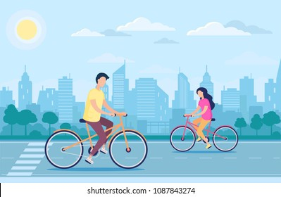 Couple young man and woman driving bicycles in the city park