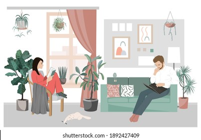 Couple of young people working and studying at home. Man working on a laptop while sitting on the sofa and woman reading a book in a chair. Lockdown and quarantine staying at home for family.