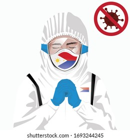 Covid-19 or Coronavirus concept. Filipino medical staff wearing mask in protective clothing and praying for against Covid-19 virus outbreak in Philippines. Filipino man and Philippines flag. Pandemic