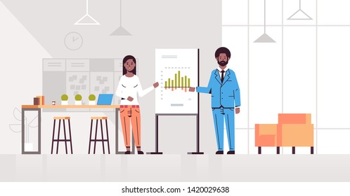 coworkers presenting financial graph on flip chart african american business couple at conference meeting making presentation concept modern office interior flat full length horizontal