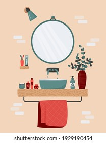 Cozy bathroom interior. Blue sink on wood counter with a large round mirror hanging above it. Vase with eucalyptus branches. Toothbrush, body care cosmetics, towel