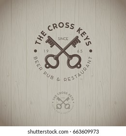 Cross keys pub logo. Two keys with letters emblems on a wood background. Keys icon.