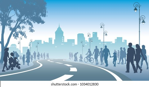 Crowd of people is walking on a street, city with high buildings in the background.