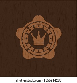 crown icon inside wooden emblem