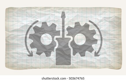 Crumpled graph paper with screwdriver and cogwheels